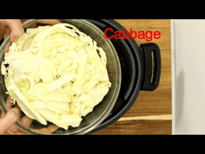 Step 2 for making slow cooker unstuffed cabbage rolls casserole is cooking cabbage and onions