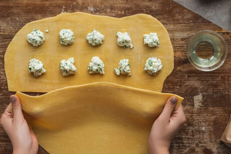 step 2 of how to make ravioli step by step = use water or egg wash to seal the edges of your two pasta dough pieces together